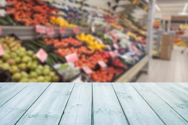 Tampo da mesa de madeira vazio no fruto borrado do mercado, loja.