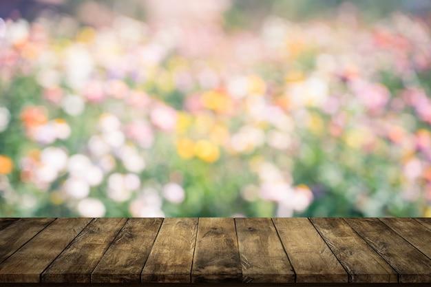 Tampo da mesa de madeira vazio no fundo borrado do jardim de flores.