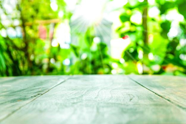 Tampo da mesa de madeira velho vazio com fundo do verde do borrão no tempo do jardim e de manhã.