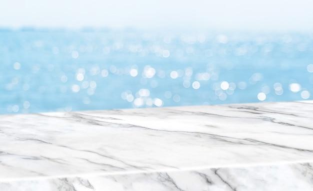 Tampo da mesa de mármore branco brilhante vazio com fundo de boekh de céu e mar de borrão