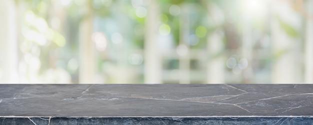 Tampo da mesa de mármore de pedra preta vazia e turva do restaurante interior com fundo de vista de janela.