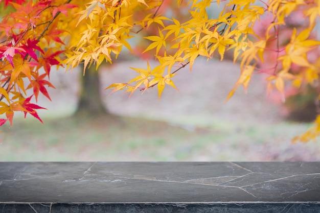 Tampo da mesa de pedra de mármore branco vazio e árvore borrada do outono e fundo vermelho da folha.