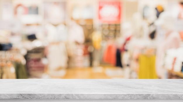 Tampo da mesa de pedra de mármore branco vazio e centro comercial com janela de vidro borrado