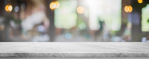 Tampo da mesa de pedra de mármore branco vazio e desfoque de vidro janela interior café e restaurante banner simulado fundo abstrato - pode ser usado para exibição ou montagem de seus produtos.