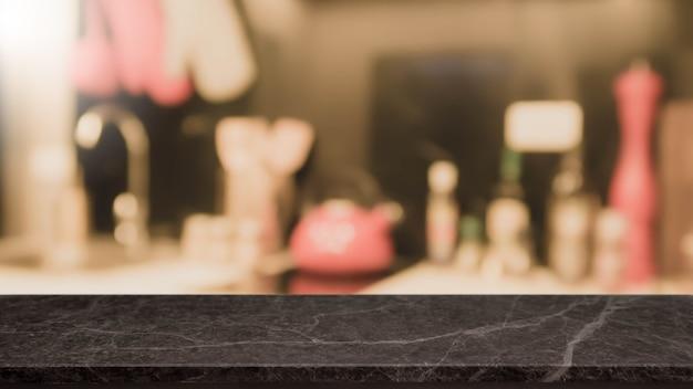 Tampo da mesa de pedra preto vazio e fundo borrado do interior da cozinha.