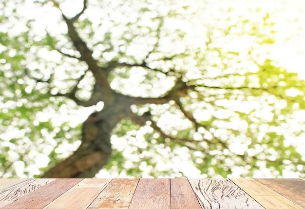 Tampo da mesa de prancha de madeira vazia com natureza verde turva deixa o fundo