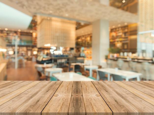 Tampo da mesa vazio da placa de madeira sobre do borrão no fundo da cafetaria.