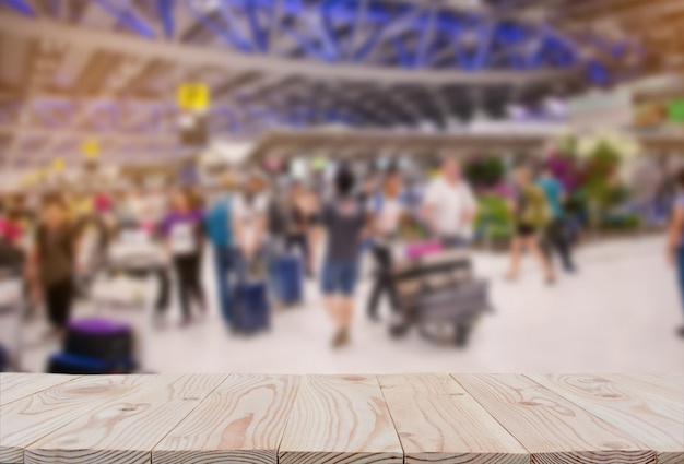 Tampo da mesa vazio da placa de madeira sobre do fundo borrado do aeroporto do terminal de passageiro.
