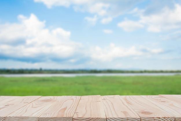 Tampo da mesa vazio da placa de madeira sobre do fundo borrado do céu azul e do rio. copie o espaço