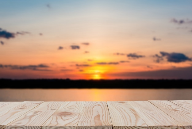Tampo da mesa vazio da placa de madeira sobre do fundo borrado do por do sol e do lago.