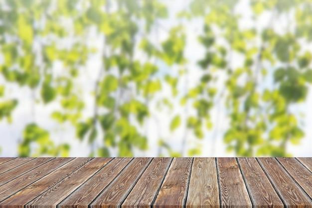 Tampo da mesa vazio no fundo borrado de ramos verdes.