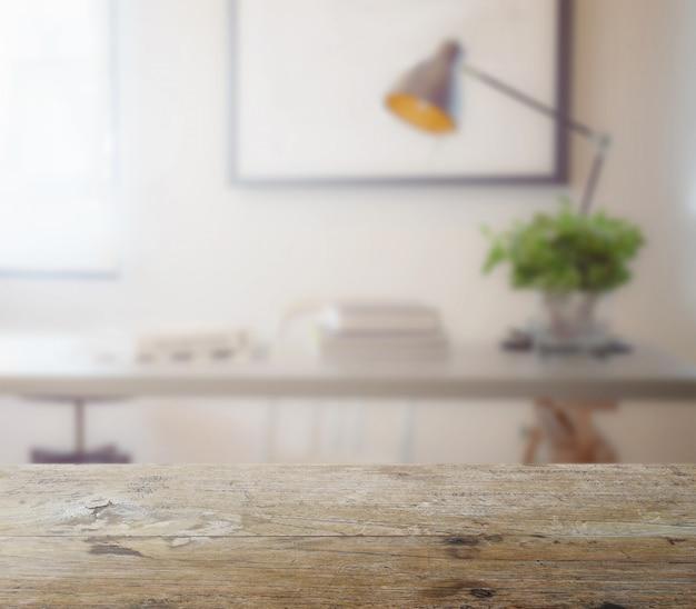 Tampo de madeira com borrão da moderna mesa de trabalho com livro e lâmpada como pano de fundo