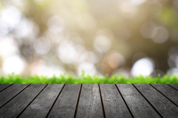 Tampo de madeira em desfoque de fundo verde de árvores no parque