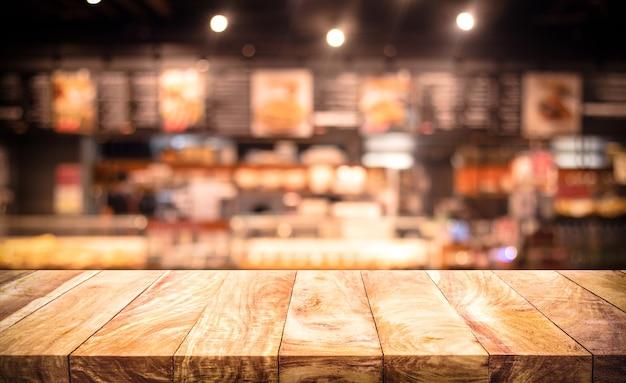 Tampo de mesa de madeira com bokeh claro desfocado em café noturno escuro