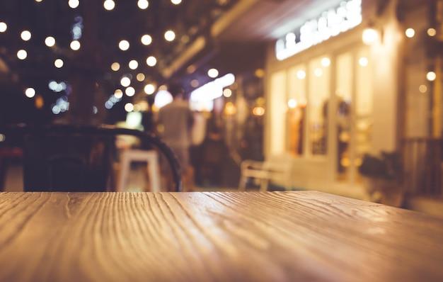 Tampo de mesa de madeira com desfoque de iluminação em café-restaurante noturno