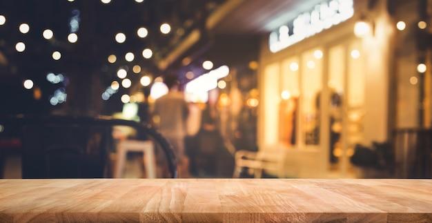 Tampo de mesa de madeira com desfoque de iluminação em um café de rua à noite
