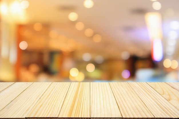 Tampo de mesa de madeira com luzes abstratas de bokeh de café e restaurante desfocado fundo desfocado