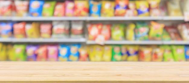 Tampo de mesa de madeira com prateleiras de lojas de conveniência de supermercado com fundo abstrato borrado de batata frita