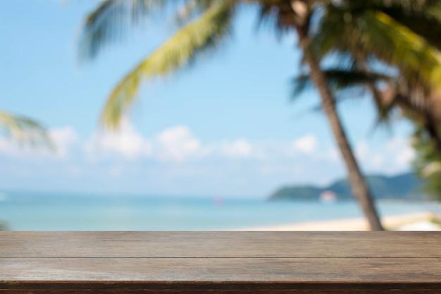 Tampo de mesa de madeira e praia de verão borrada e fundo de céu Foto Premium