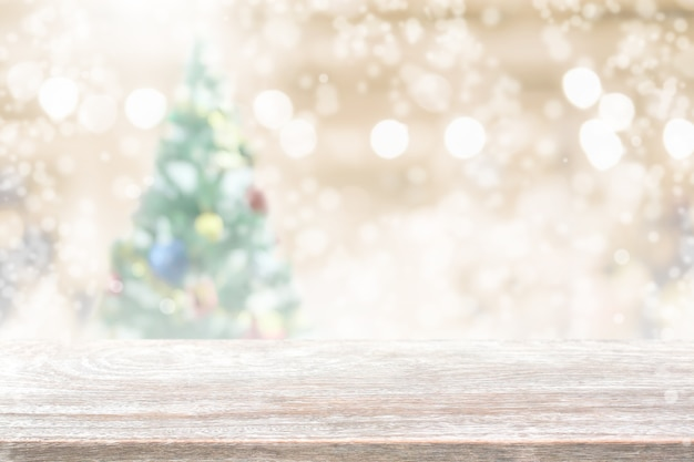 Tampo de mesa de madeira em borrão com fundo de árvore de natal bokeh com queda de neve - pode ser usado para exibir ou montar seus produtos.