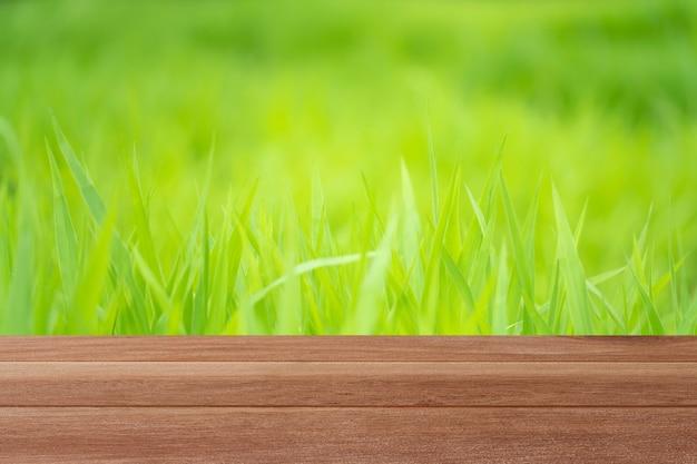 Tampo de mesa de madeira em fundo verde borrado no jardim para montagem de seus produtos