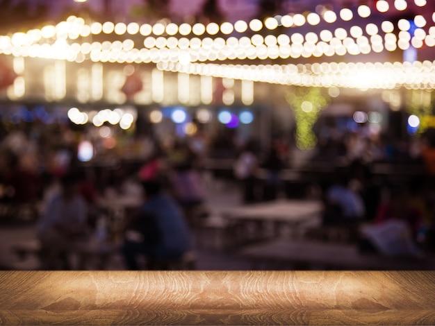 Tampo de mesa de madeira em restaurante noturno desfocado para ponto de encontro de festa noturna