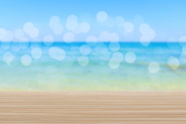 Tampo de mesa de madeira no fundo desfocado da praia com bokeh - pode ser usado para exibir ou montar seus produtos