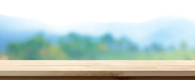 Tampo de mesa de madeira sobre floresta verde borrada e fundo de montanha, banner panorâmico