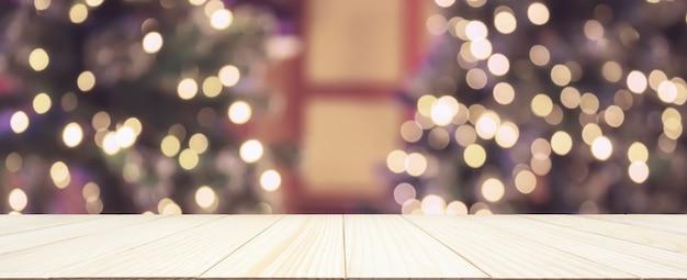 Tampo de mesa de madeira vazio com árvore de natal borrada