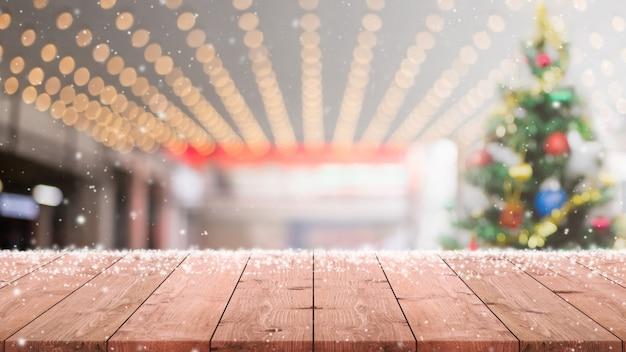 Tampo de mesa de madeira vazio com árvore de natal desfocada