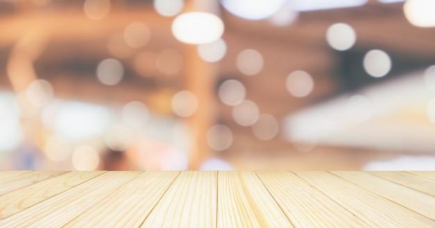 Tampo de mesa de madeira vazio com café restaurante com luzes abstratas bokeh desfocado desfocado