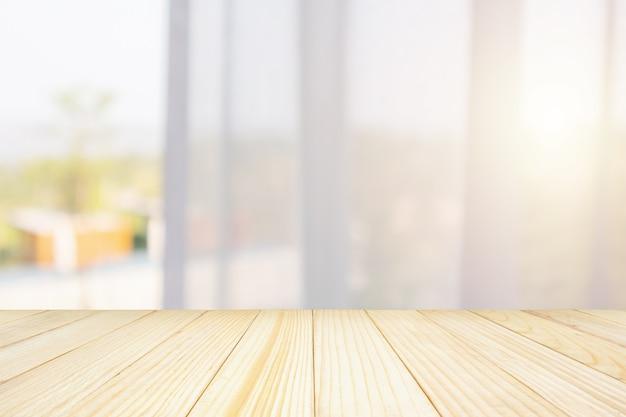 Tampo de mesa de madeira vazio com fundo de borrão abstrato de cortina de janela para exposição de produto