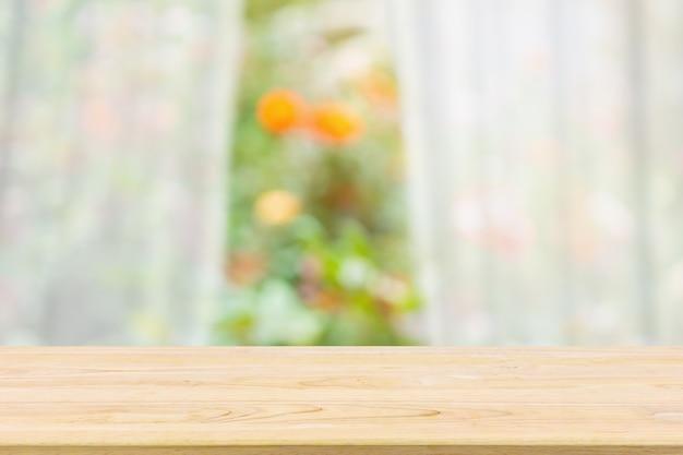 Tampo de mesa de madeira vazio com janela de cortina branca borrada e fundo verde de jardim para modelo de exibição de produto