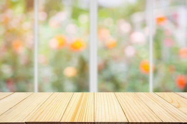 Tampo de mesa de madeira vazio com janela de cozinha desfocar o fundo