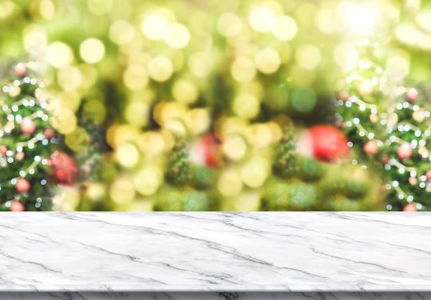 Tampo de mesa de mármore branco com fundo de árvore de natal borrão abstrato com luz bokeh