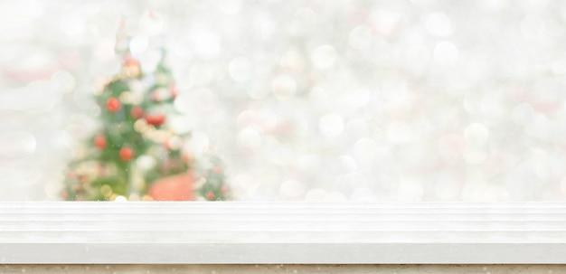 Tampo de mesa de mármore branco na decoração de árvore de natal de bokeh borrão com fundo de luz de seqüência de caracteres