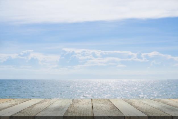Tampo vazio da mesa de madeira no mar azul