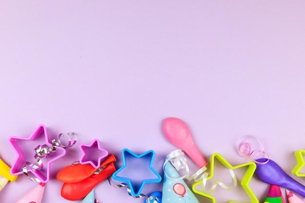 Tampões, balão e estrelas da festa de anos no fundo roxo. fundo colorido da celebração com vários partido.