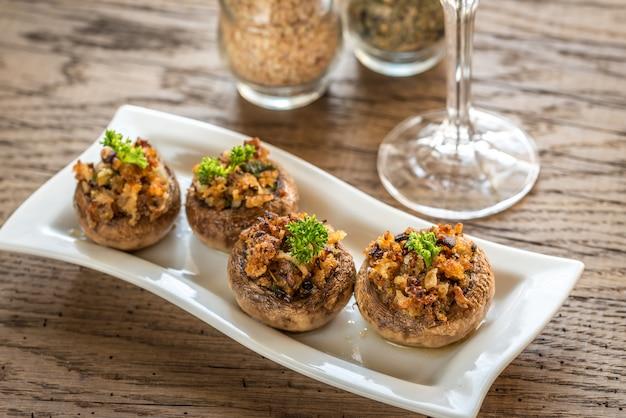 Tampões de cogumelos recheados com mistura de queijo, cebola e pão