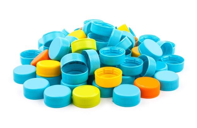 Tampões de garrafa plásticos coloridos no fundo branco.