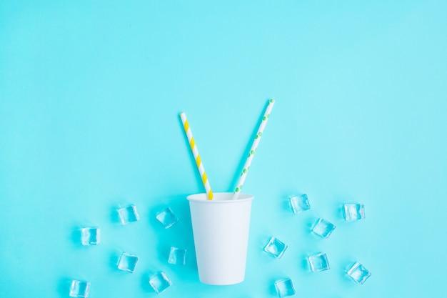 Tampões de papel branco com palha cocktail de cor sobre fundo azul.