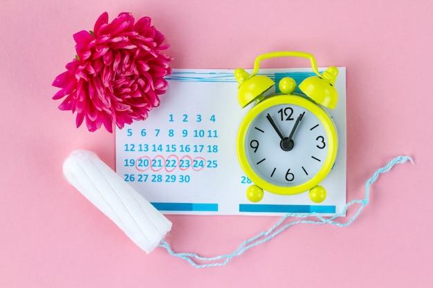 Tampões para menstruação, despertador, calendário feminino e uma flor rosa. cuidados de higiene em dias críticos. ciclo menstrual regular.