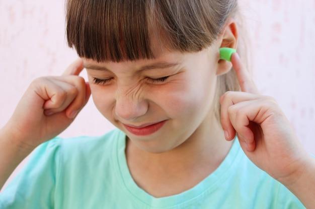 Tampões para os ouvidos para proteger contra o ruído. garota cobriu os ouvidos.