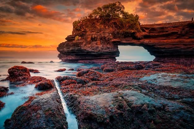 Tanah lot temple no mar no por do sol na ilha de bali, indonésia.