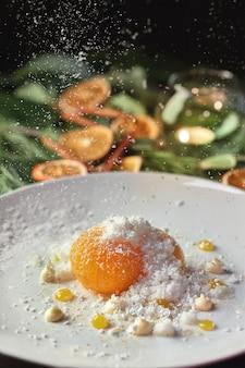 Tangerina caramelizada com flocos de coco no fundo e enfeites de natal