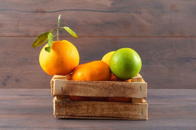 Tangerina de fruta laranja e limão verde em caixa de madeira na superfície marrom