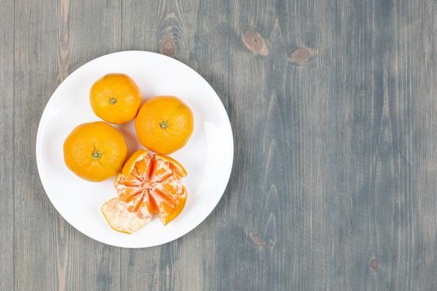 Tangerina descascada com tangerinas inteiras em prato branco