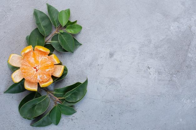 Tangerina descascada e folhas decorativas em fundo de mármore.