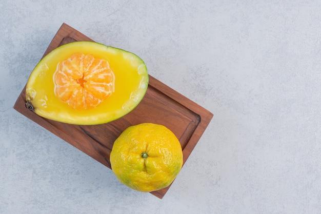 Tangerina fresca, suculenta e orgânica na placa de madeira.