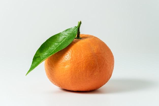 Tangerina ou clementina com folha verde isolada na superfície branca